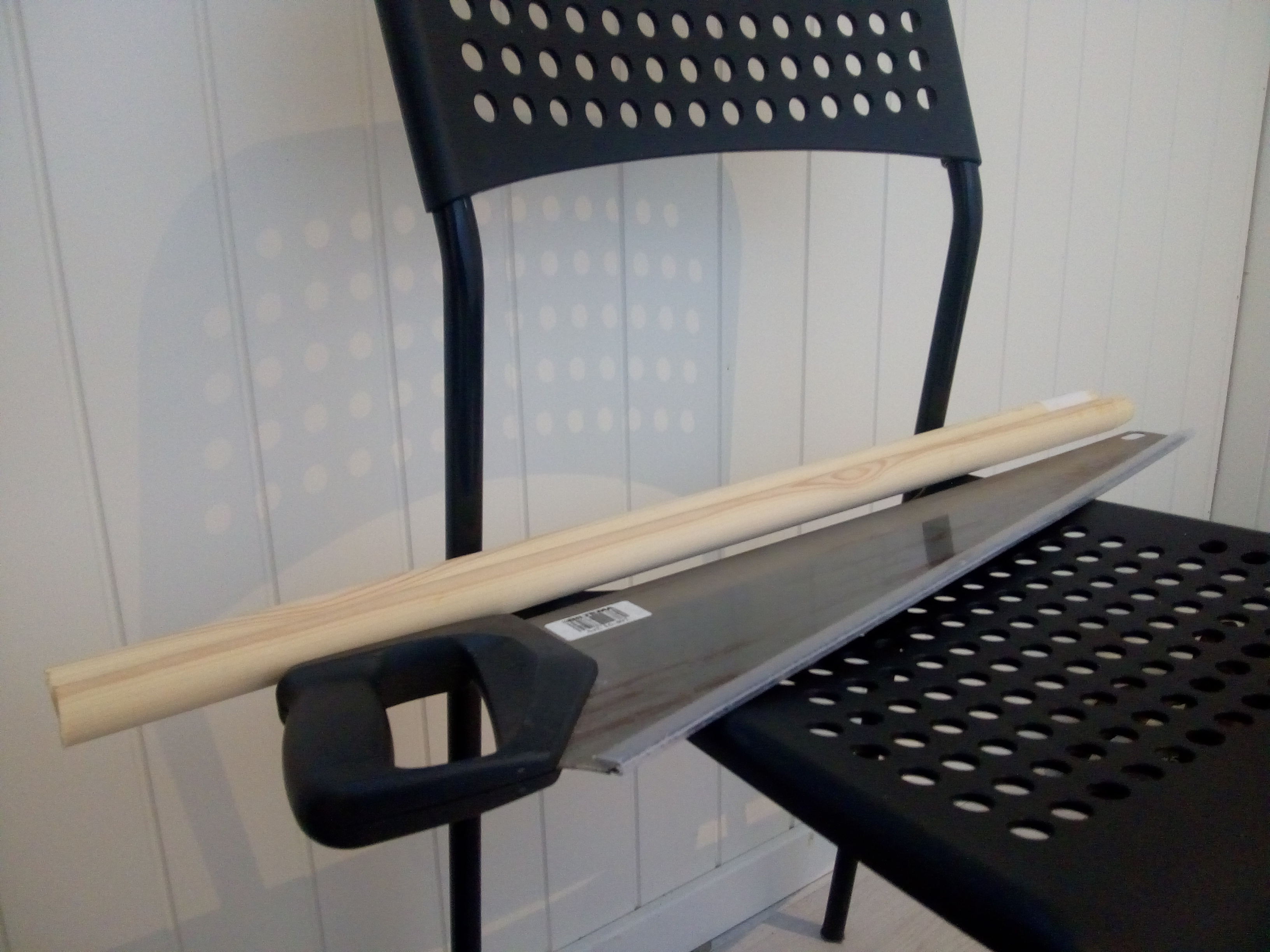 Broom handle cut and saw, on a chair