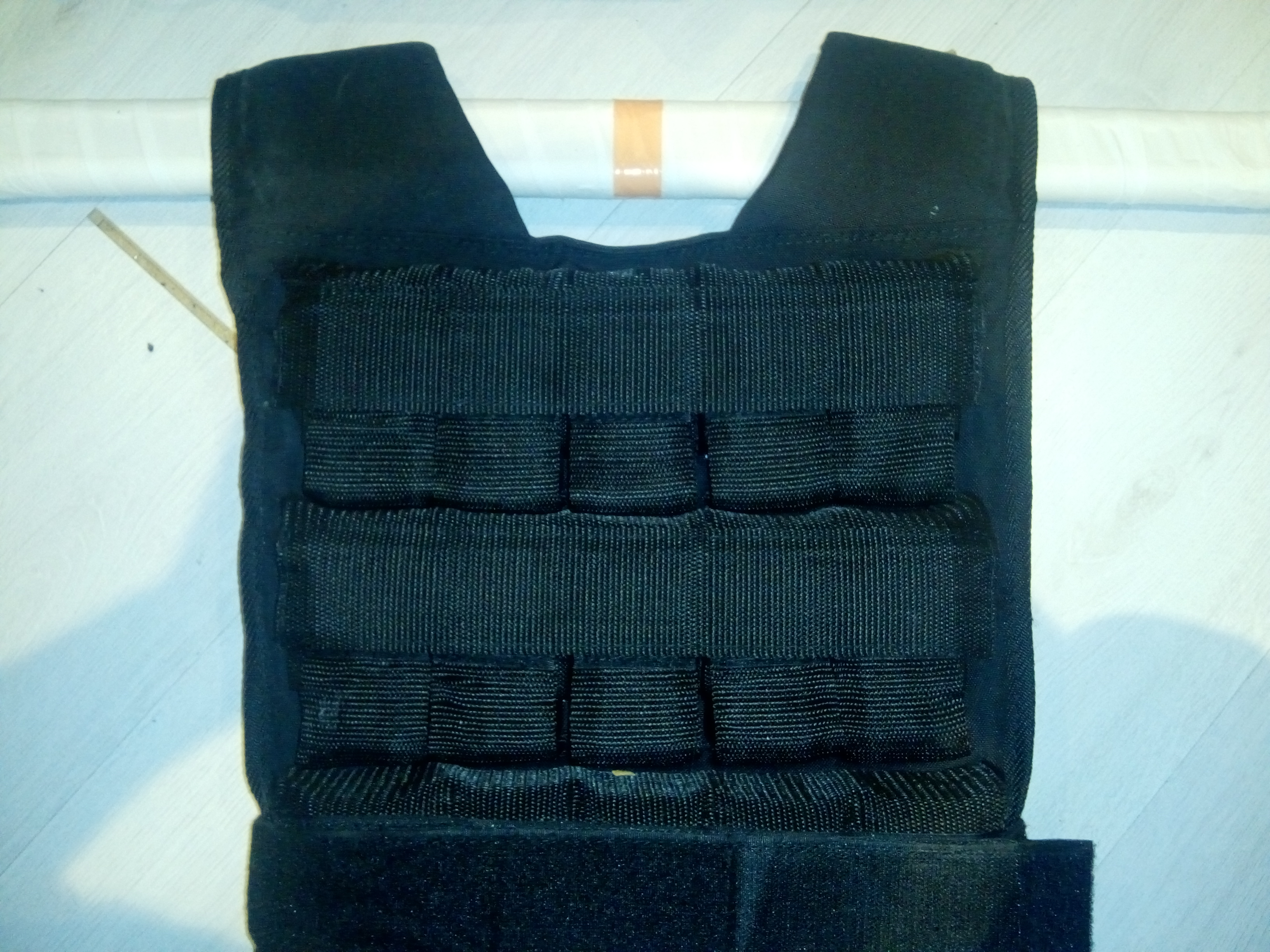 Lifting bar thread through the weighted vest